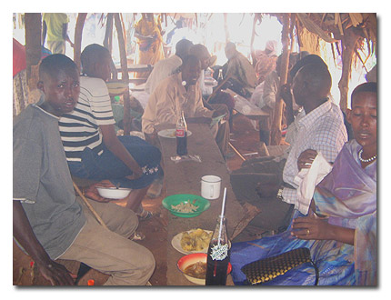 Herdsmen eat in a kafunda after selling cattle in Nakitoma market